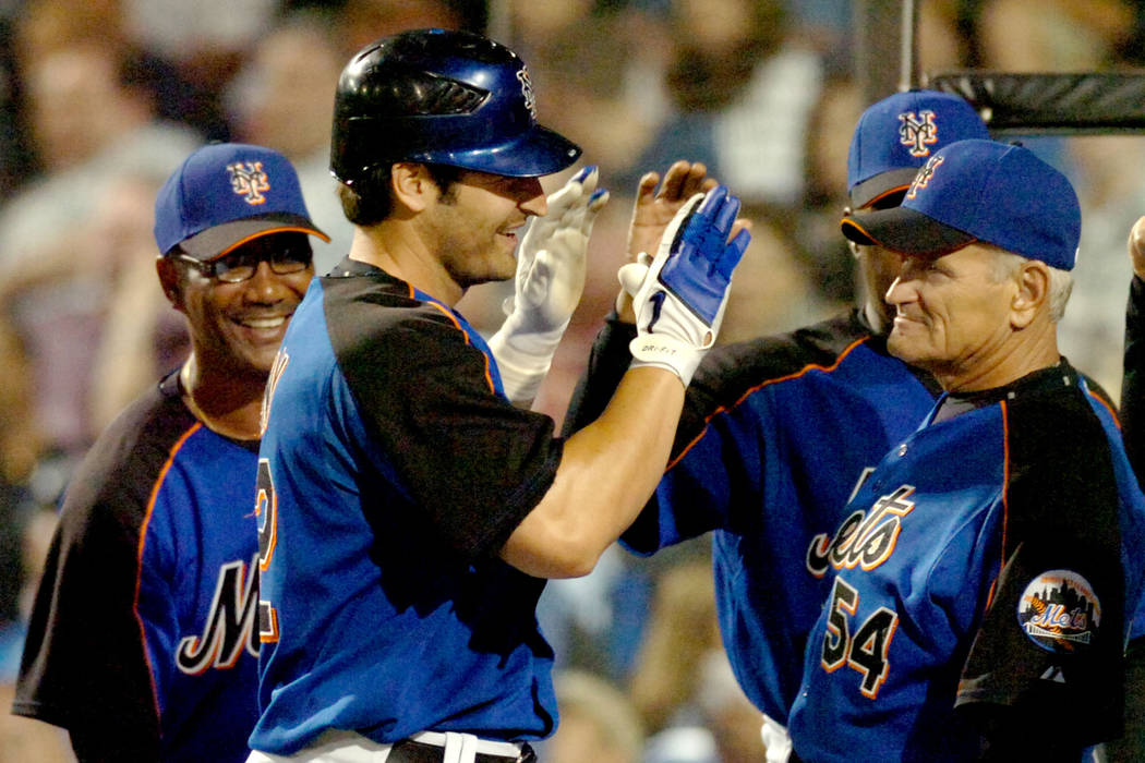New York Mets' Xavier Nady, center is congratulated at the dugout by coaches including coach Rick Down (54) after hitting a third inning home run against the Washington Nationals during a spring t ...