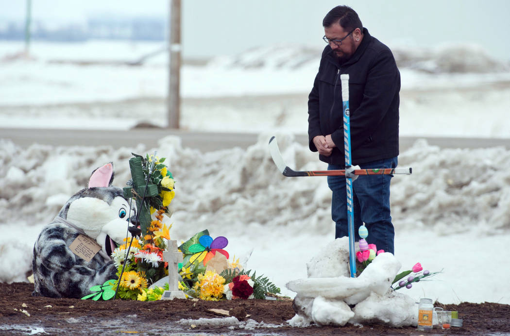 A man pays at a memorial, including a cross made out of hockey sticks, near the intersection of a fatal bus crash near Tisdale, Saskatchewan, Canada, Monday, April, 9, 2018. A bus carrying the Hum ...