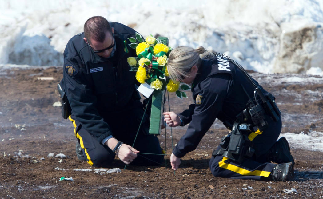 Members of the Royal Canadian Mounted Police lay flowers at the intersection of a crash site near Tisdale, Saskatchewan, Sunday, April, 8, 2018. A bus carrying the Humboldt Broncos hockey team cra ...