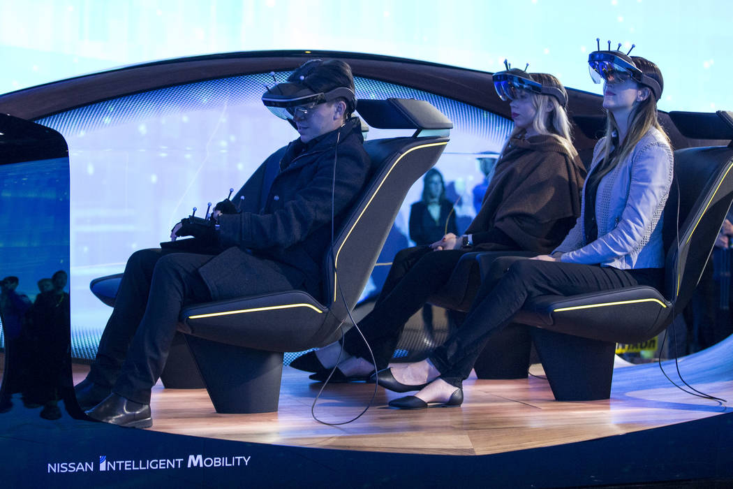 Attendees take part in a demo for autonomous driving innovations at the Nissan Intelligent Mobility booth on day one of CES at the Las Vegas Convention Center in Las Vegas on Tuesday, Jan. 8, 2019 ...
