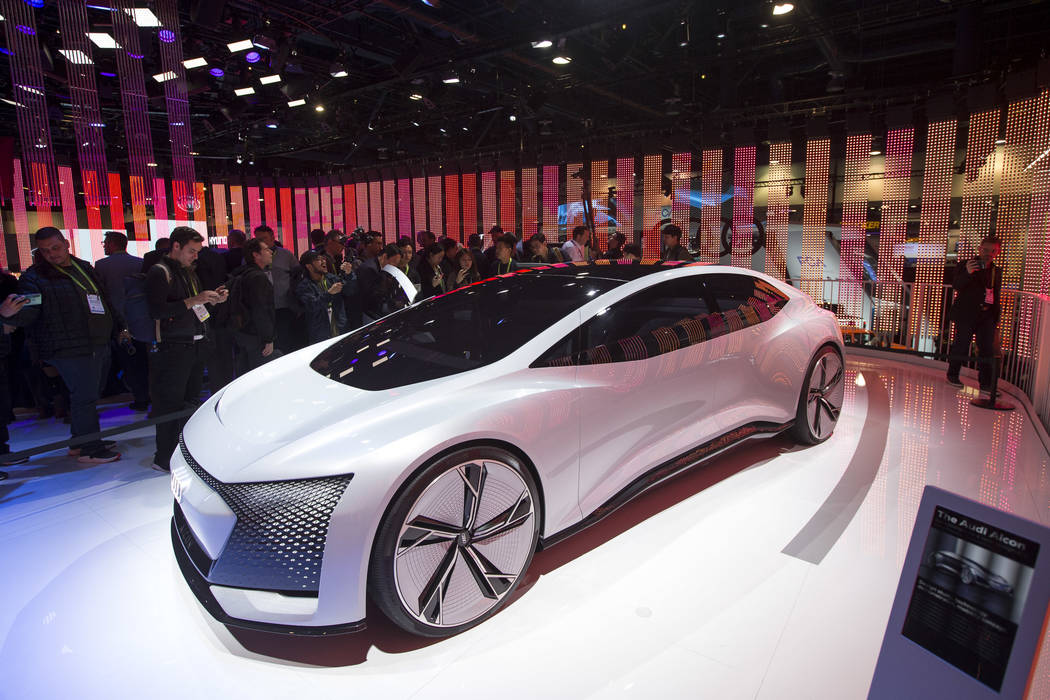 Attendees browse over the Audi Aicon, a fully autonomous concept car due out in 2021, on display on day one of CES at the Las Vegas Convention Center in Las Vegas on Tuesday, Jan. 8, 2019. Richard ...