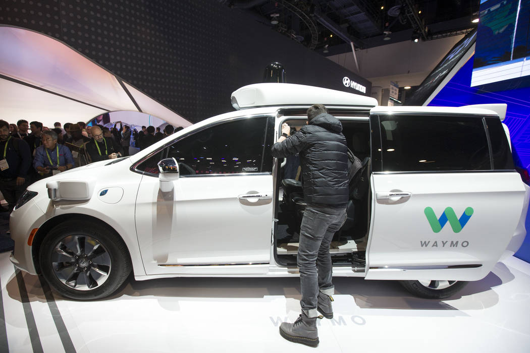 Attendees browse over a self-driving car by Waymo, Google's sister company, on display at the Fiat Chrysler Automobiles booth on day one of CES at the Las Vegas Convention Center in Las Vegas on T ...