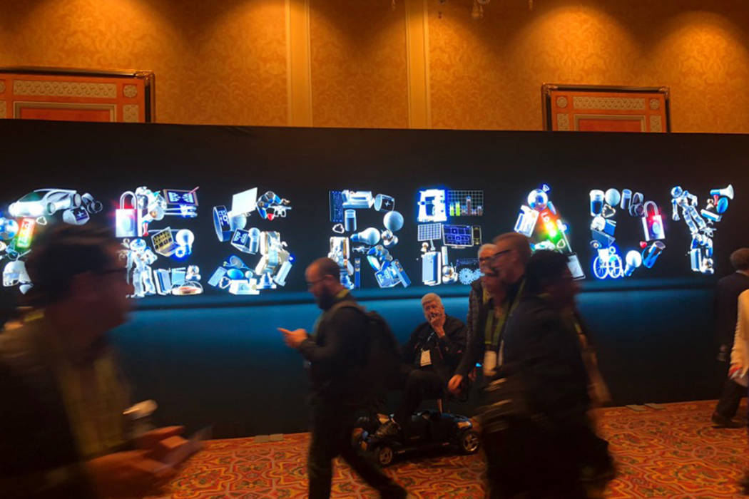 Attendees of CES in Las Vegas walk past a sign on Tuesday, Jan. 8, 2019. (Caroline Brehman/Las Vegas Review-Journal)