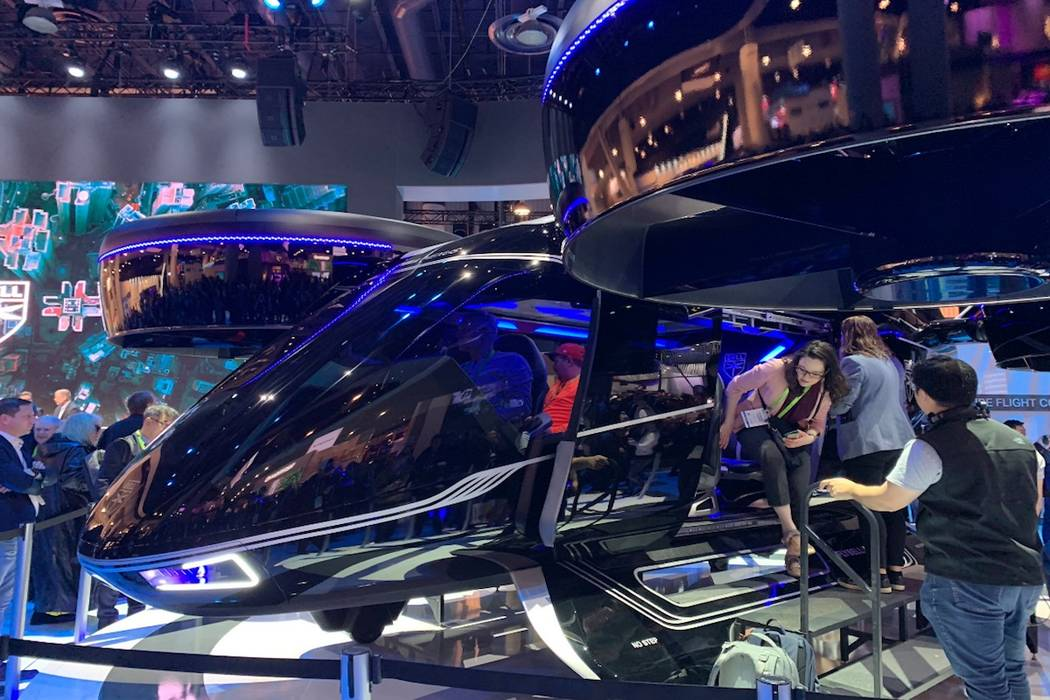 """CES attendees look at a model of Bell's """"flying taxi"""" that Uber plans to have in the air in Los Angeles, Dallas and an international city in 2020 for testing purposes and 2023 commercially. ..."""