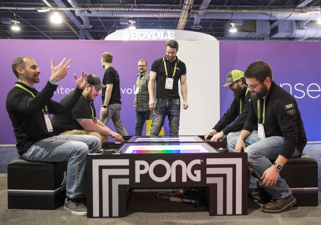 Nik Birge, left, celebrates after beating Joe Miller in a game of Pong during the first day of CES 2019 on Tuesday, Jan. 8, 2019, at the Las Vegas Convention Center, in Las Vegas. The four day tec ...