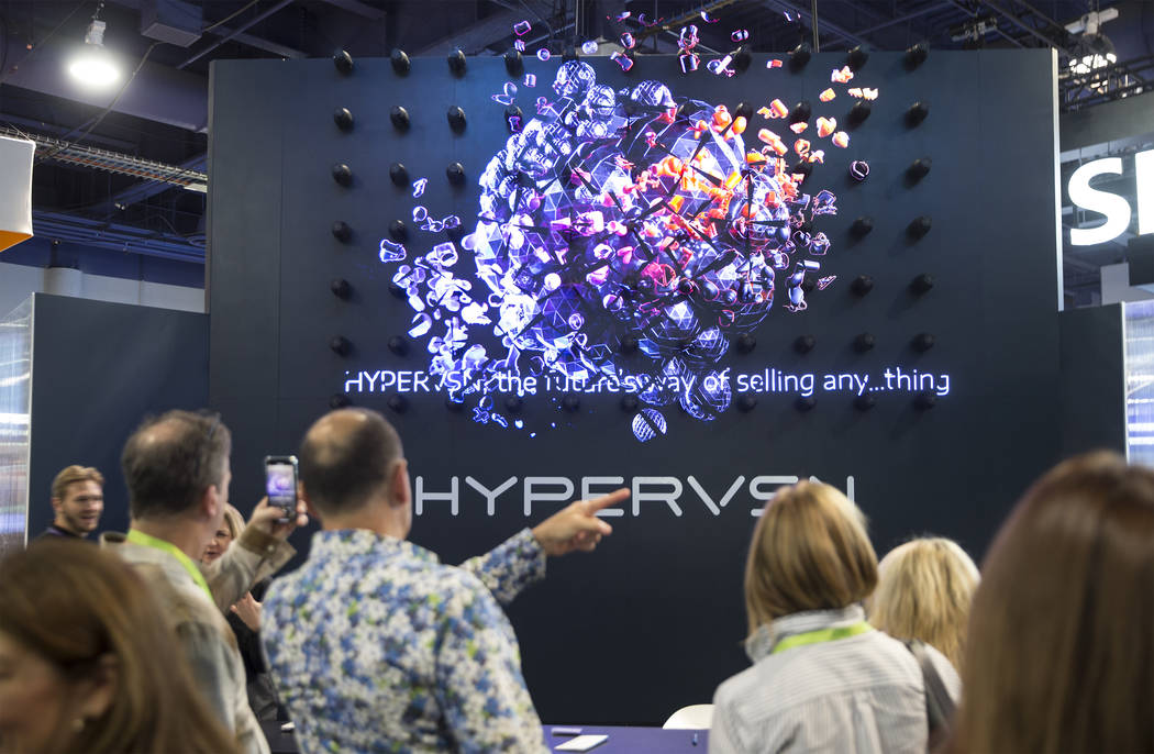 Convention goers explore the Hypervsn 3D holographic display during the first day of CES 2019 on Tuesday, Jan. 8, 2019, at the Las Vegas Convention Center, in Las Vegas. The four day tech event br ...