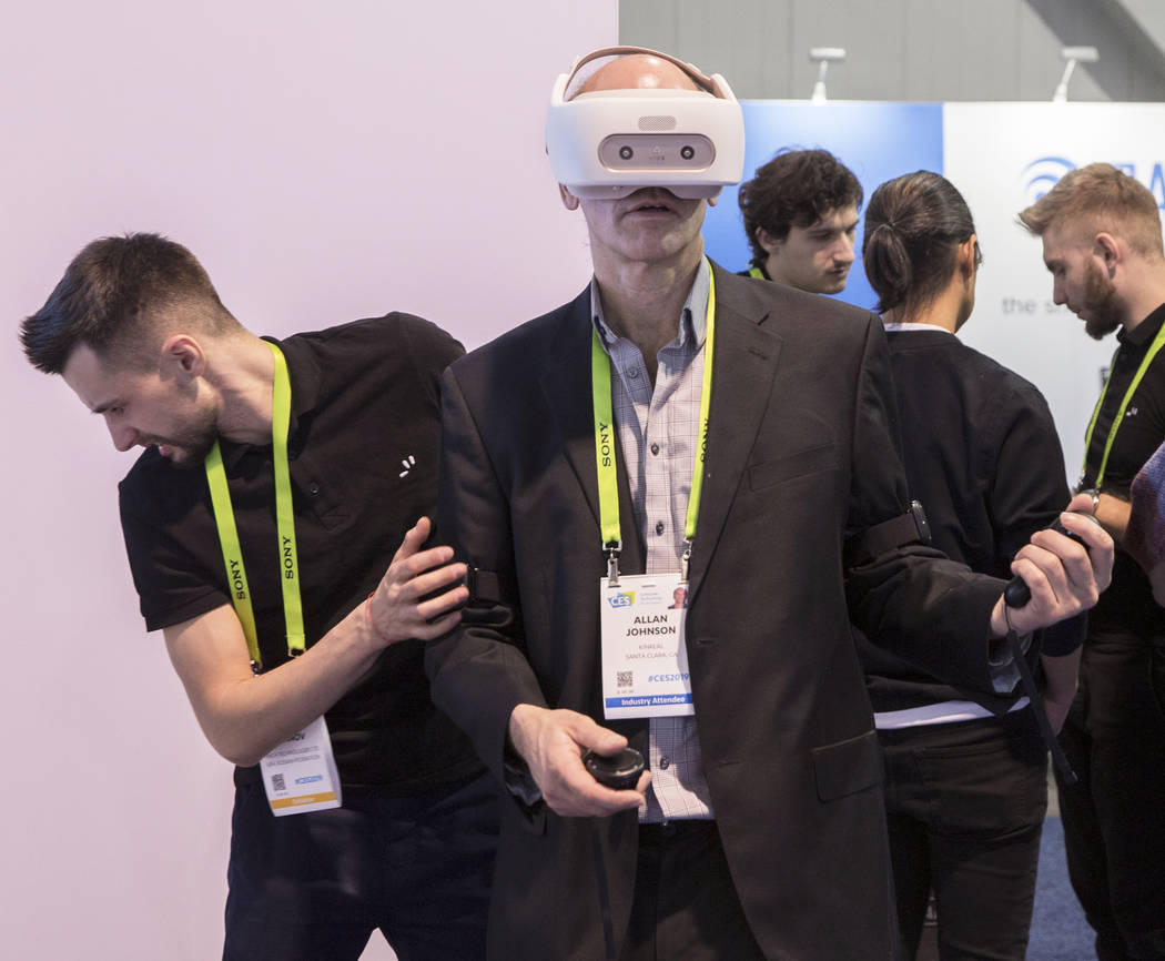 Allan Johnson, middle, explores a virtual reality simulator from Finch Technologies during the first day of CES 2019 on Tuesday, Jan. 8, 2019, at the Las Vegas Convention Center, in Las Vegas. The ...