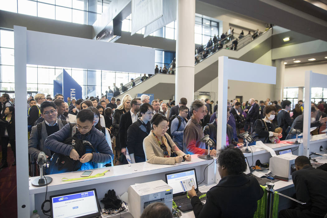 People pick up their credentials in the South Hall during the first day of CES 2019 on Tuesday, Jan. 8, 2019, at the Las Vegas Convention Center, in Las Vegas. The four day tech event brings over ...
