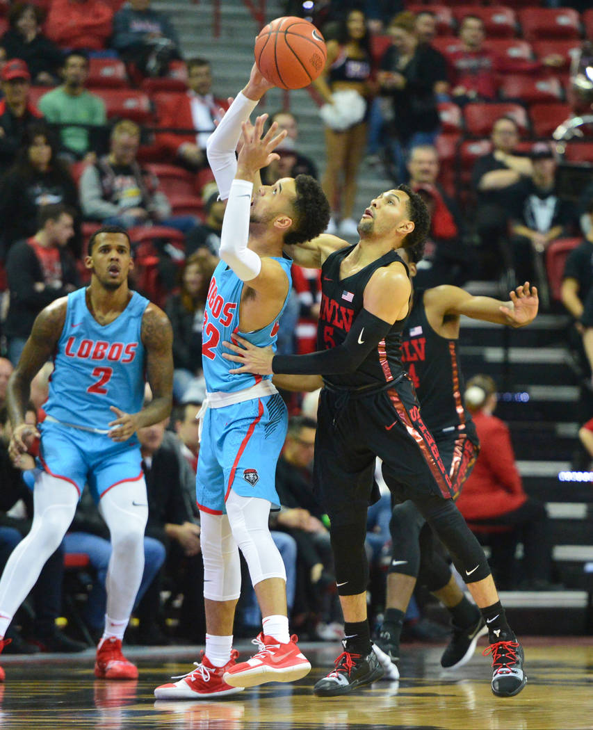 UNLV Rebels guard Noah Robotham (5) tips the ball away from New Mexico Lobos guard Anthony Mathis (32) during the first half of the UNLV Rebels and the New Mexico Lobos NCAA basketball game at the ...