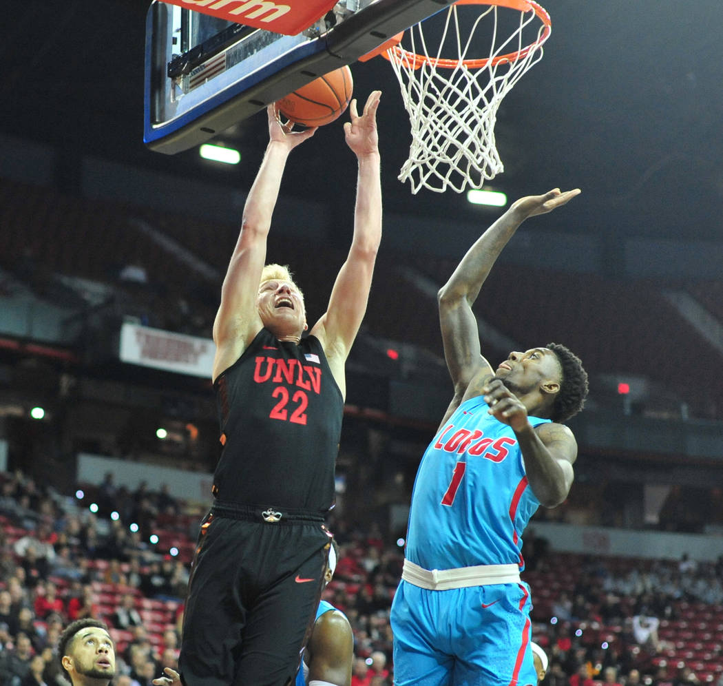 UNLV Rebels guard Trey Woodbury (22) shoots the ball over New Mexico Lobos forward Corey Manigault (1) during the first half of the UNLV Rebels and the New Mexico Lobos NCAA basketball game at the ...