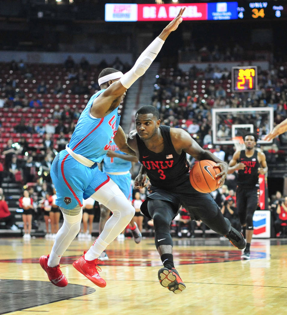 UNLV Rebels guard Amauri Hardy (3) dribbles the ball around New Mexico Lobos guard Keith McGee (3) during the first half of the UNLV Rebels and the New Mexico Lobos NCAA basketball game at the Tho ...