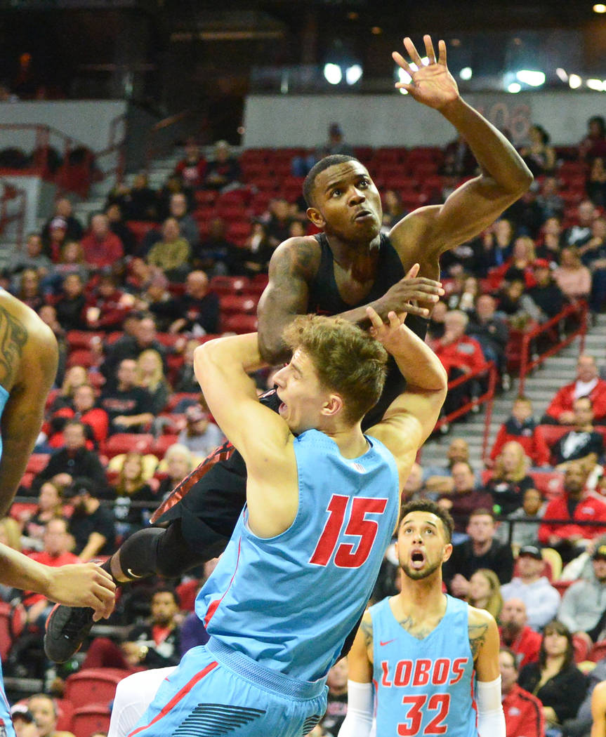 UNLV Rebels guard Amauri Hardy (3) collides with New Mexico Lobos center Vladimir Pinchuk (15) during the second half of the UNLV Rebels and the New Mexico Lobos NCAA basketball game at the Thomas ...