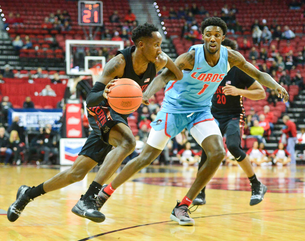 UNLV Rebels guard Kris Clyburn (1) dribbles the ball past New Mexico Lobos forward Corey Manigault (1) during the second half of the UNLV Rebels and the New Mexico Lobos NCAA basketball game at th ...