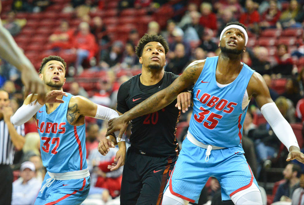 UNLV Rebels forward Nick Blair (20) fights for a free-throw rebound against New Mexico Lobos guard Anthony Mathis (32) and forward Carlton Bragg (35) during the second half of the UNLV Rebels and ...