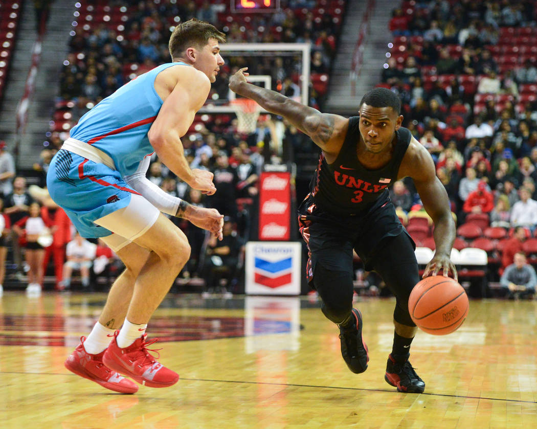 UNLV Rebels guard Amauri Hardy (3) dribbles the ball past New Mexico Lobos forward Dane Kuiper (14) during the first half of the UNLV Rebels and the New Mexico Lobos NCAA basketball game at the Th ...