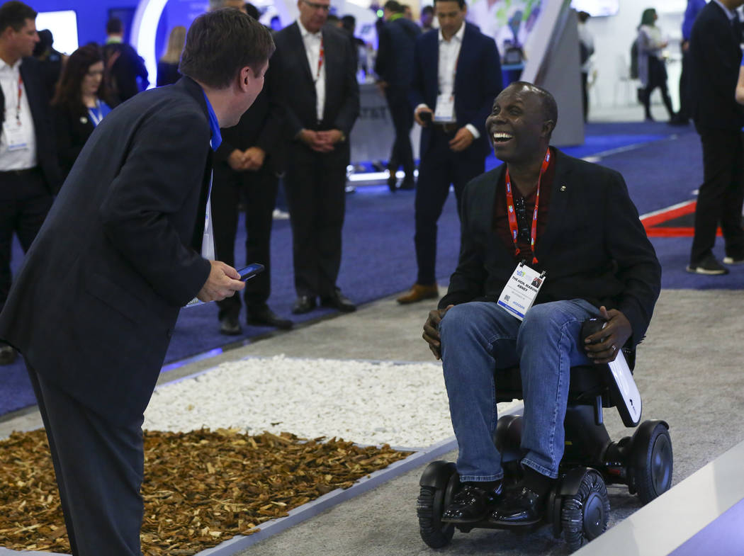 Rhode Island state Rep. Marvin Abney laughs while trying out a Whill wheelchair using autuonomous capabilities at the Sands Expo and Convention Center during CES in Las Vegas on Tuesday, Jan. 8, 2 ...
