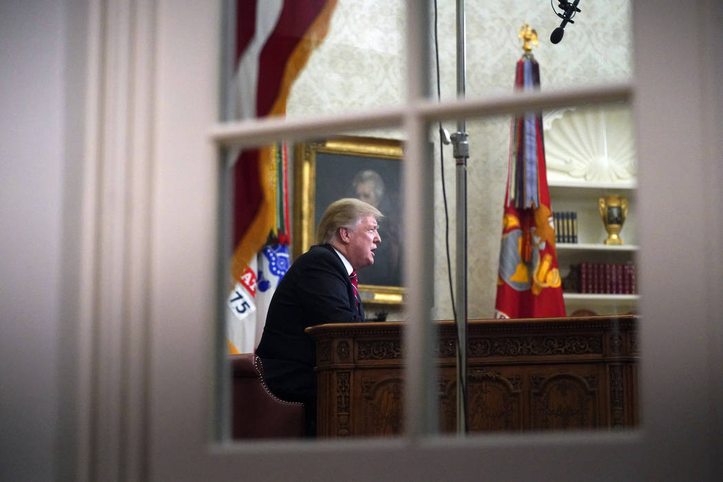 As seen from a window outside the Oval Office, President Donald Trump gives a prime-time address about border security Tuesday, Jan. 8, 2018, at the White House in Washington. (AP Photo/Carolyn Ka ...