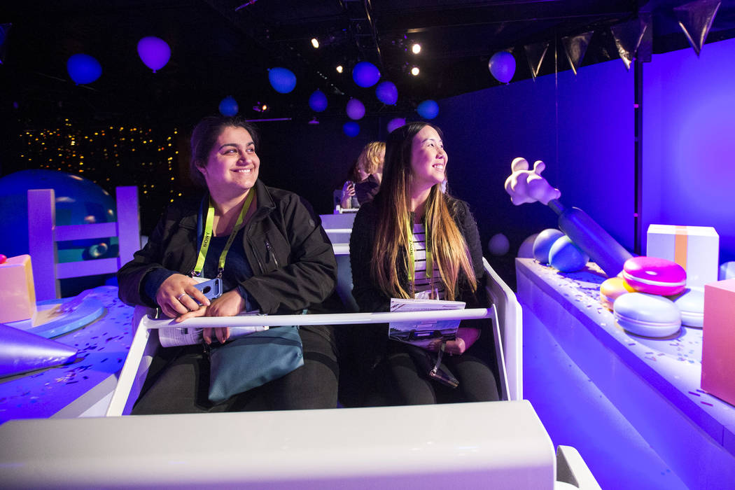 Attendees Azin Biatani, left, and Sabrina Nguyen, with the Fullerton College in Calif., take a spin on an amusement ride promoting the Google Assistant, Google's artificial intelligence-powered vi ...