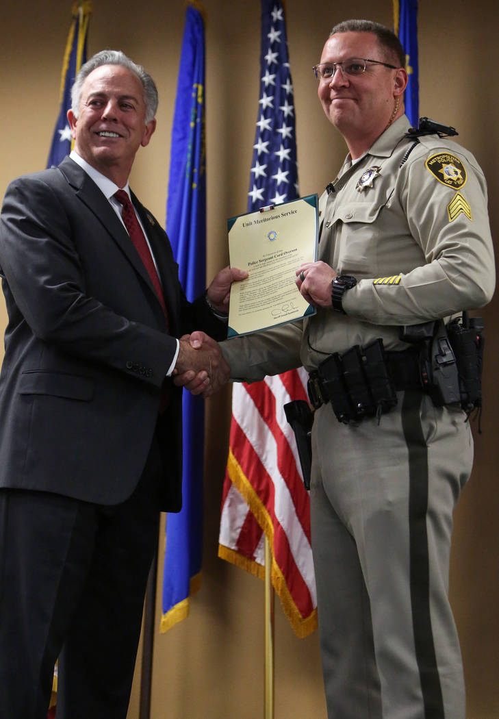 Clark County Sheriff Joe Lombardo presents Sgt. Cord Overson with the Unit Meritorious Award at the Las Vegas Metropolitan Police Department headquarters in Las Vegas, Wednesday, Jan. 9, 2019. Car ...