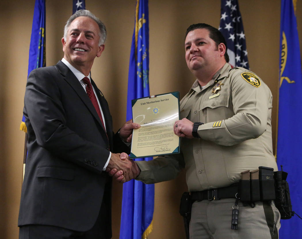 Clark County Sheriff Joe Lombardo presents Officer Michael Nolan with the Unit Meritorious Award at the Las Vegas Metropolitan Police Department headquarters in Las Vegas, Wednesday, Jan. 9, 2019. ...