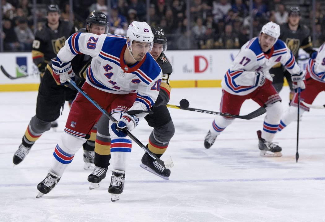 New York Rangers left wing Chris Kreider and Vegas Golden Knights center Oscar Lindberg battle for the puck during the first period of an NHL hockey game Tuesday, Jan. 8, 2019, in Las Vegas. (AP P ...