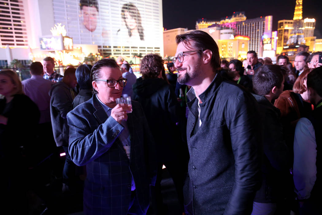 Anthony Penta, of Miami Beach, Florida, left, and Lukasz Gajdzis of Poland mingle on the Terrace in Omnia Nightclub at Caesars Palace in Las Vegas at the CES Opening Party Tuesday, Jan. 8, 2019. K ...