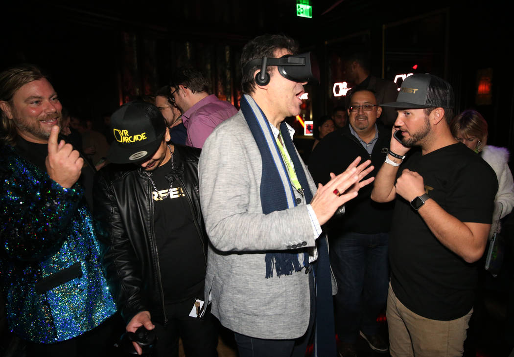 Las Vegas Review-Journal columnist John Katsilometes, second from right, experiences virtual reality as Chris Crescitelli, founder of VR Fest Las Vegas, left, looks on during the CES Opening Party ...