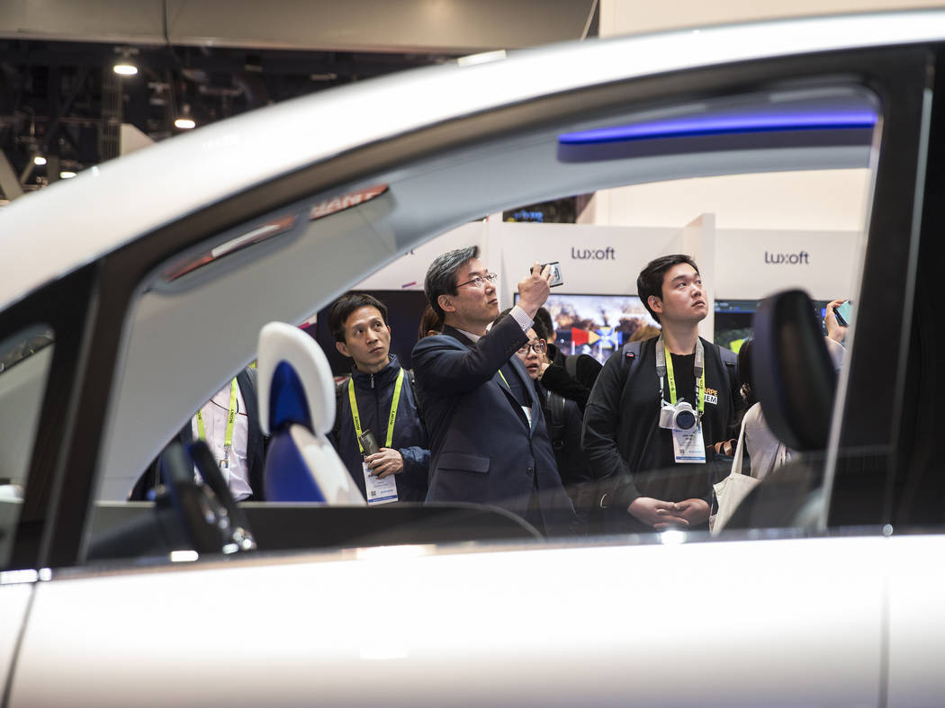 Convention goers watch a presentation from AISIN autonomous cars during the second day of CES 2019 on Wednesday, Jan. 9, 2019, at the Las Vegas Convention Center, in Las Vegas. The four day tech e ...