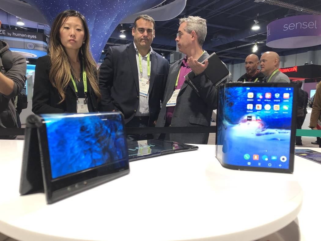 CES 2019 attendees examine Royole's Flex Pai, the first commercial folding phone. (Bailey Schulz/Las Vegas Review-Journal)