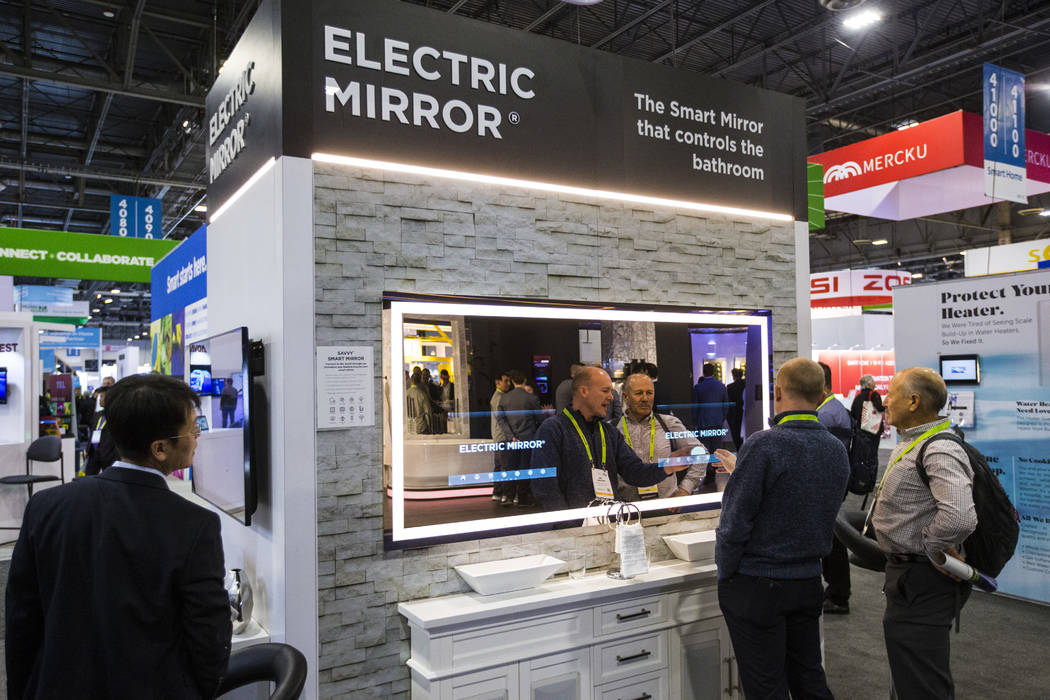 Jim Mischel, center, and Gordon van Zuiden, right, look at an Electric Mirror, featuring controls and a display built into a mirror display, the Sands Expo and Convention Center during CES in Las ...