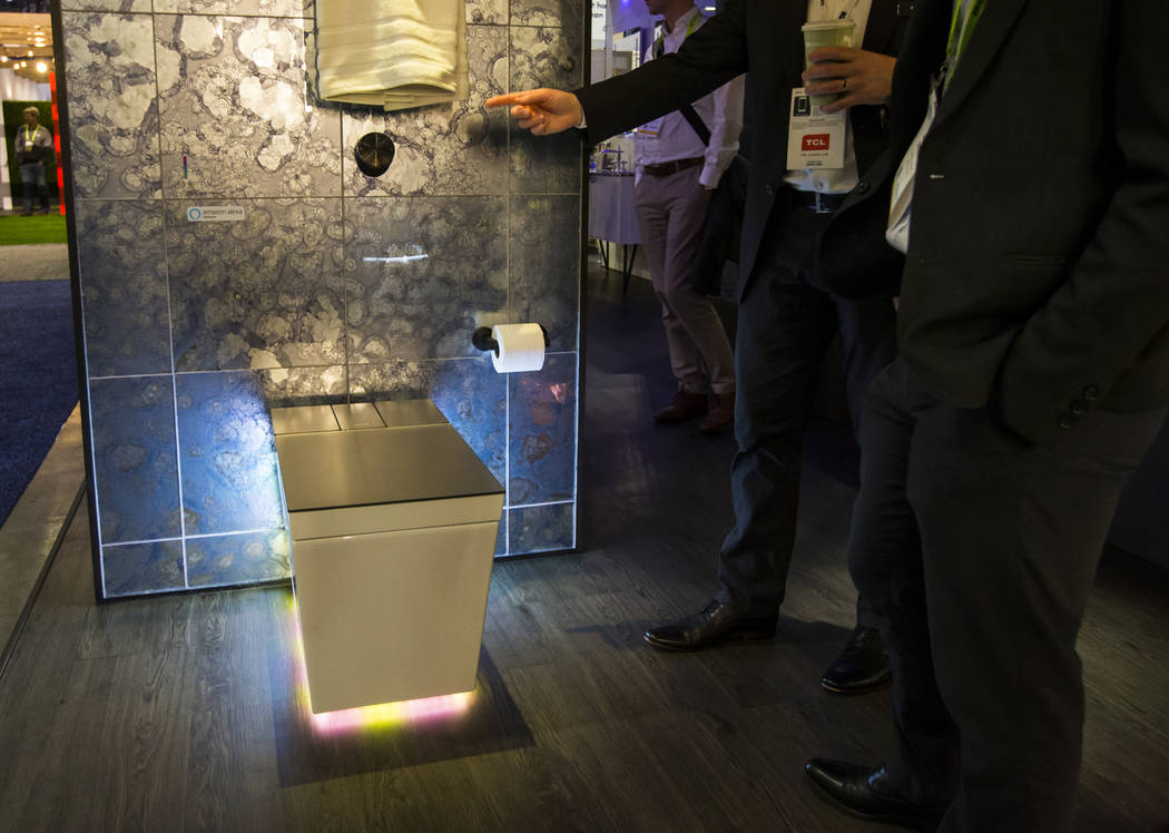 Attendees look at the Numi 2.0 intelligent toilet by Kohler at the Sands Expo and Convention Center during CES in Las Vegas on Wednesday, Jan. 9, 2019. The toilet offers voice control via Alexa, m ...