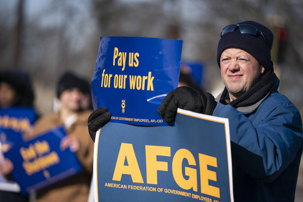 Brian Garthwaite, an FDA compliance officer who is currently furloughed and president of the American Federation of Government Employees Local 3381, holds up signs during the rally to highlight th ...
