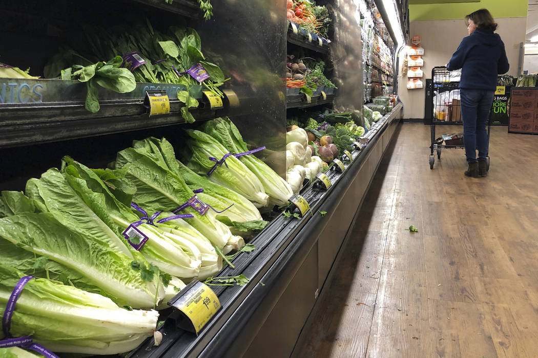 Romaine lettuce sits on the shelves as a shopper walks through the produce area of an Albertsons market in Simi Valley, Calif. on Nov. 20, 2018. (AP Photo/Mark J. Terrill, File)