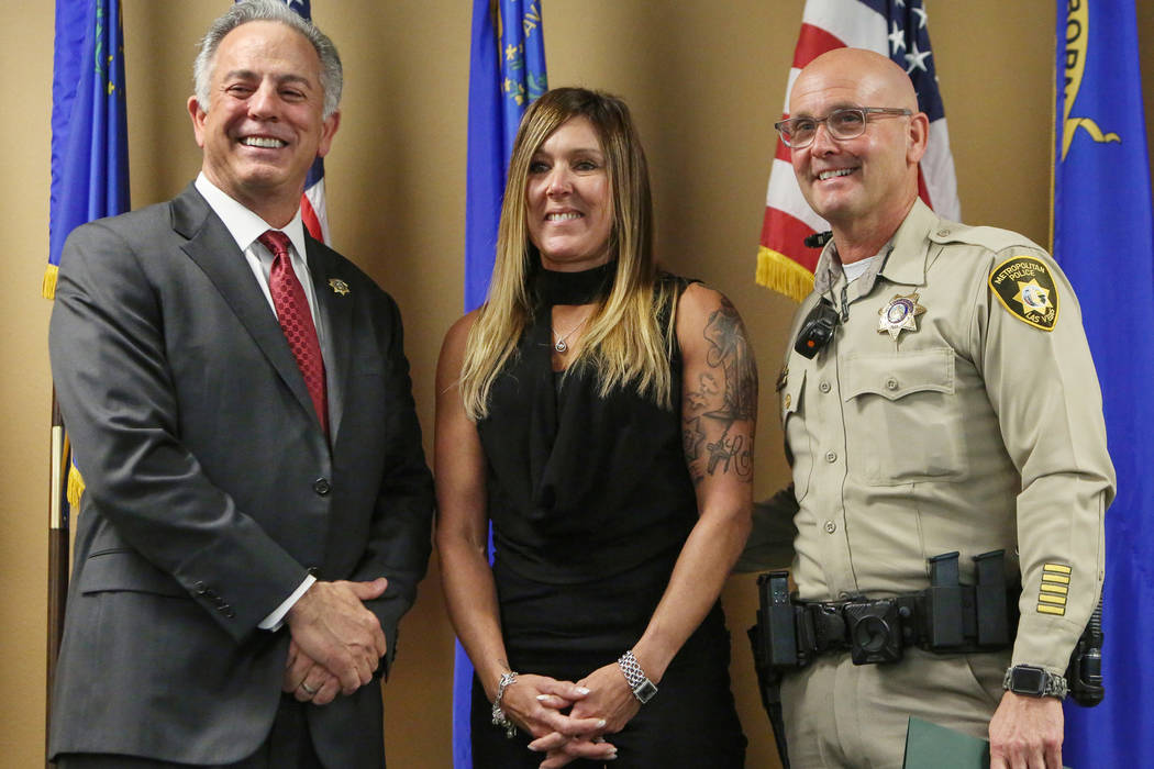 Officer Anthony Dellorso, right, stands next to Jody Ansell, center, whose life he saved during the Oct. 1, 2017, shooting as he is honored by Clark County Sheriff Joe Lombardo, left, with the Lif ...