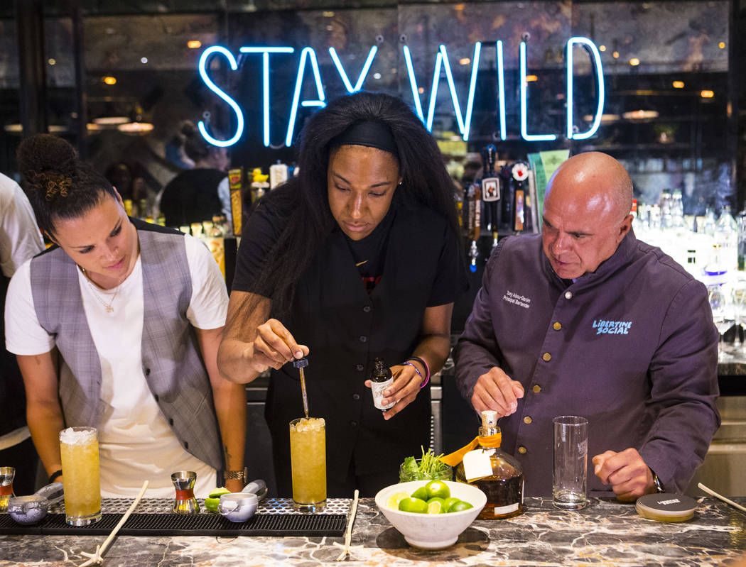 Las Vegas Aces player Kelsey Bone, center, adds bitters to a Summer Swizzle cocktail with the help of mixologist Tony Abou-Ganim. right, as teammate Kayla McBride looks on at Libertine Social in t ...