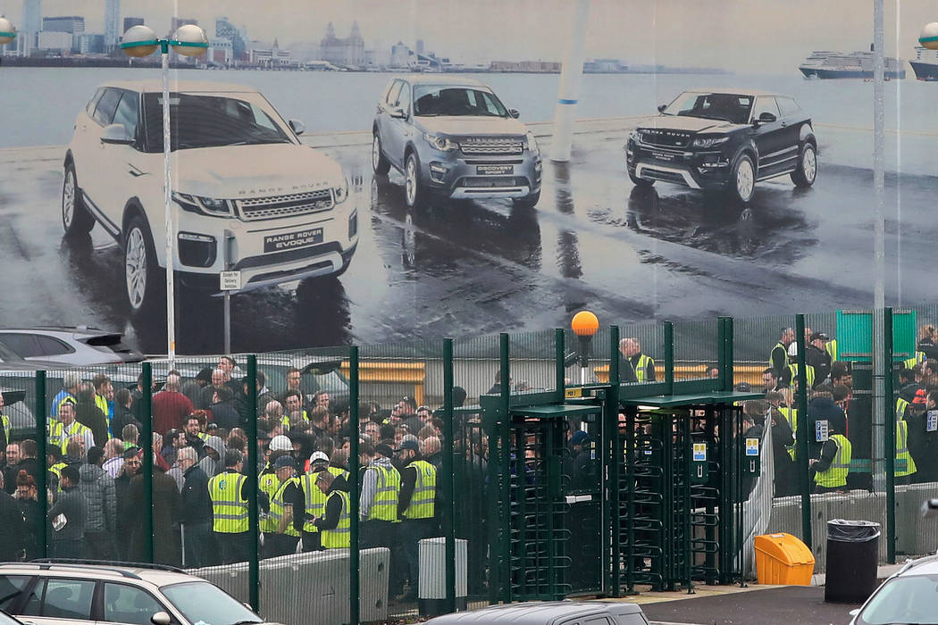 Staff gather inside the gates of the Jaguar Land Rover site in Halewood near Liverpool, England, Thursday Jan. 10, 2019. According to media reports, Jaguar Land Rover is widely expected to announ ...