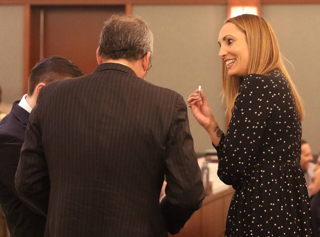 Attorney Alexis Plunkett, right, who prosecutors say bragged about putting a hit on her former boyfriend in prison, smiles as she speaks to her lawyers, Michael Becker, center, and Adam Solinger p ...