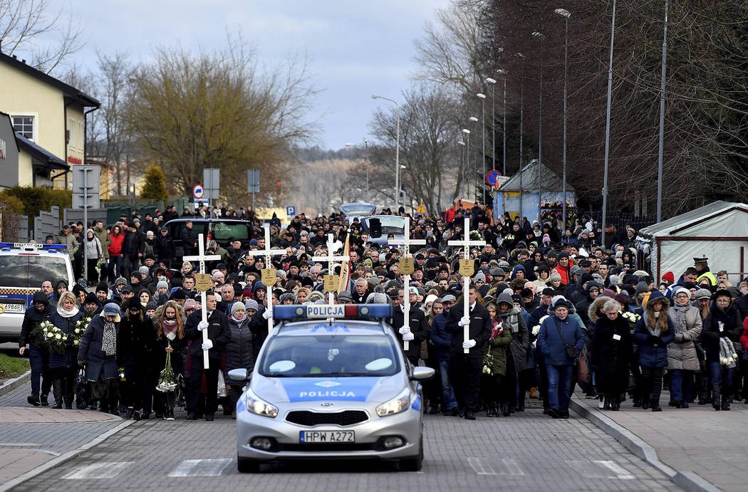 A police car leading hundreds of residents walking to the cemetery to take part in the burial of five girls who died in an entertainment escape room fire last week, in Koszalin, northern Poland, o ...