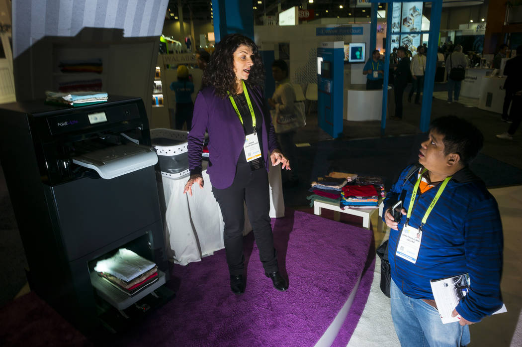 Debbie Cohen-Abravanel, center, talks about the laundry-folding robot Foldimate, left, with attendee Jonathan Albert Vallar at the Sands Expo and Convention Center during CES in Las Vegas on Thurs ...