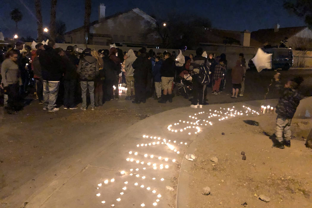 A child stands holding balloon near candles arranged to spell the name of 16-year-old Aneas King at a vigil on Thursday, January 10, 2019. The boy was fatally shot at the location of the vigil, Sa ...