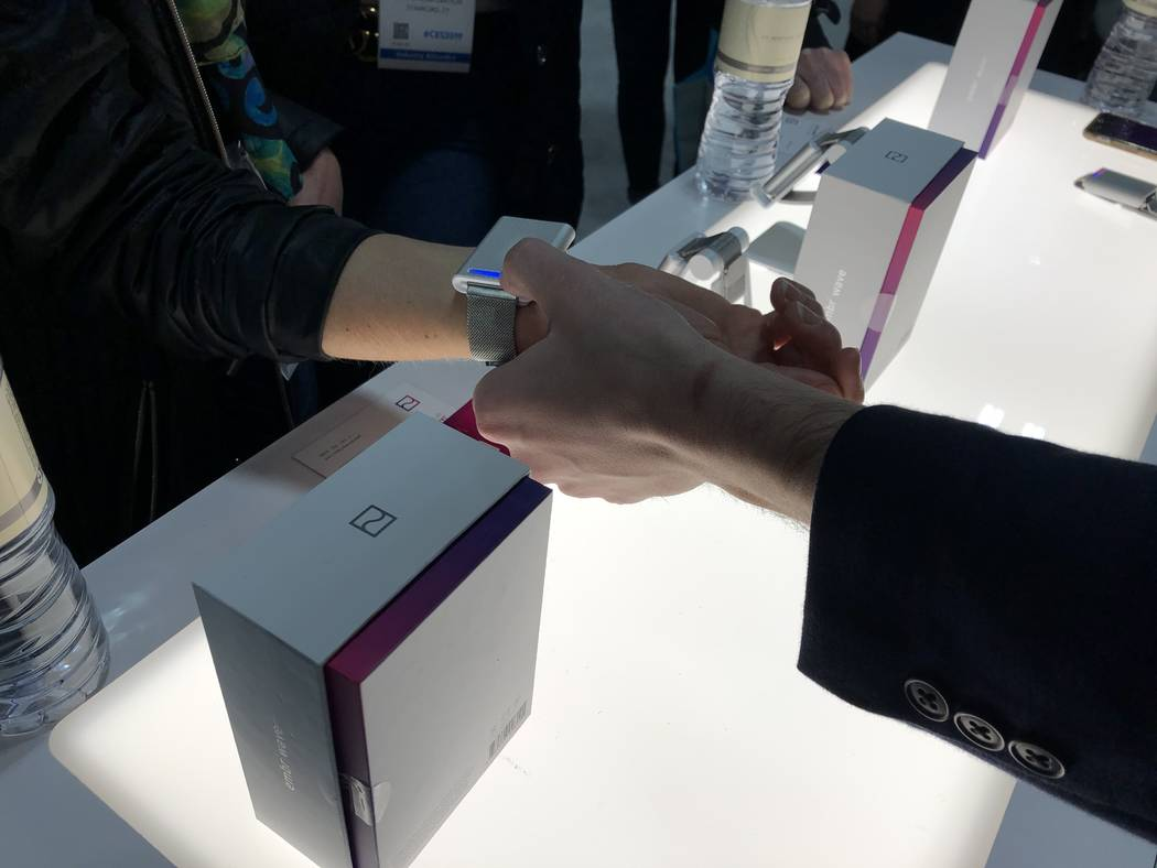 Embr Labs vice president of marketing Jake Abrams fits a CES 2019 attendee with an Embr Wave bracelet. The device makes the wearer feel five degrees warmer or cooler and sells in the U.S. and Cana ...