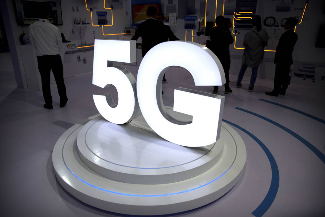 FILE- In this Sept. 26, 2018, file photo visitors stand near a 5G logo at a display the PT Expo in Beijing. AT&T has drawn ridicule by relabeling the network used by some of its phones as &#x2 ...