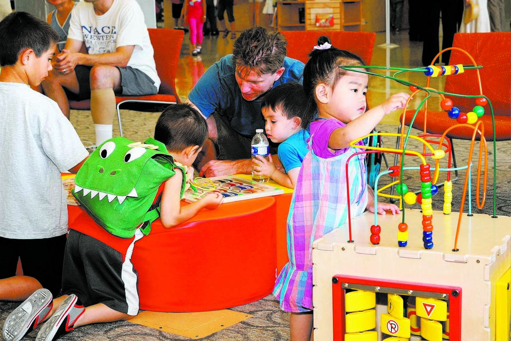 Children and adults play in the children's section at the Windmill Library, 7060 W. Windmill Lane, in Las Vegas. The library plans to offer a series of five Family Place Parent-Child Workshops for ...