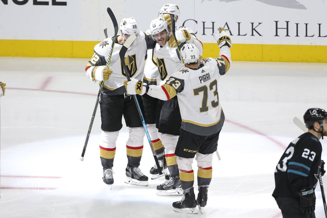 Vegas Golden Knights defenseman Jon Merrill (15), center, is swarmed by teammates after scoring against the San Jose Sharks during the third period of an NHL hockey game at T-Mobile Arena in Las V ...