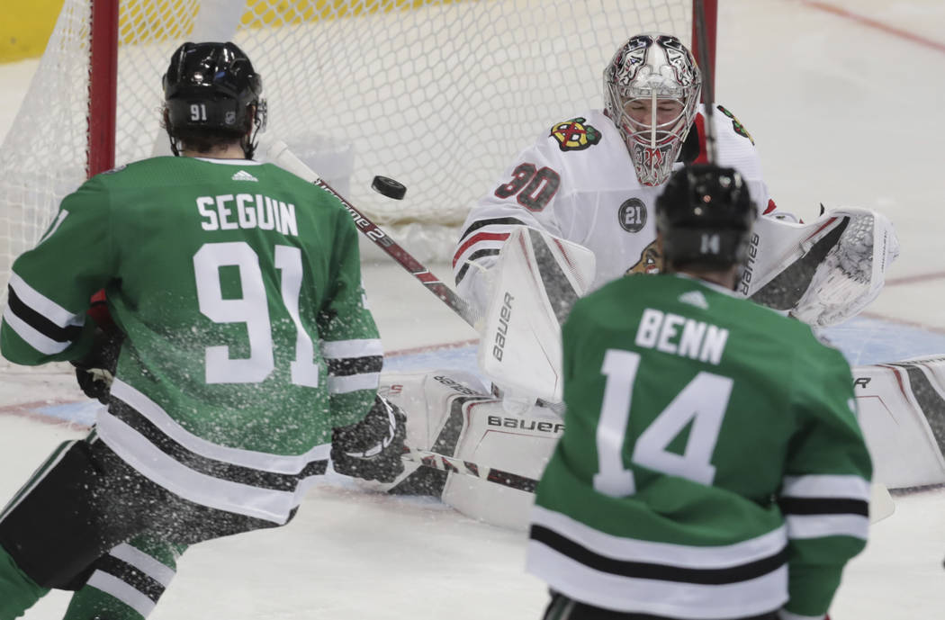 Chicago Blackhawks goaltender Cam Ward (30) defends the goal against Dallas Stars center Tyler Seguin (91) and left wing Jamie Benn (14) during the first period of an NHL hockey game in Dallas, Th ...