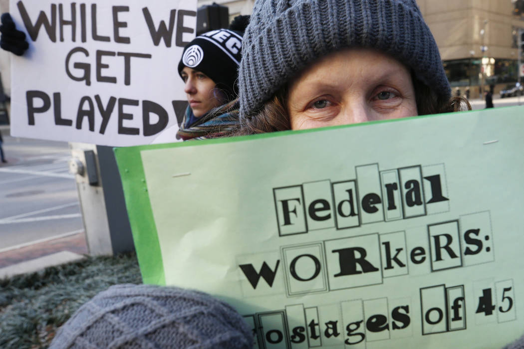 Esther Anastasia holds a sign during a protest rally with government workers and their supporters in Boston, Friday, Jan.11, 2019. The workers rallied with Democratic U.S. Sen. Ed Markey and other ...