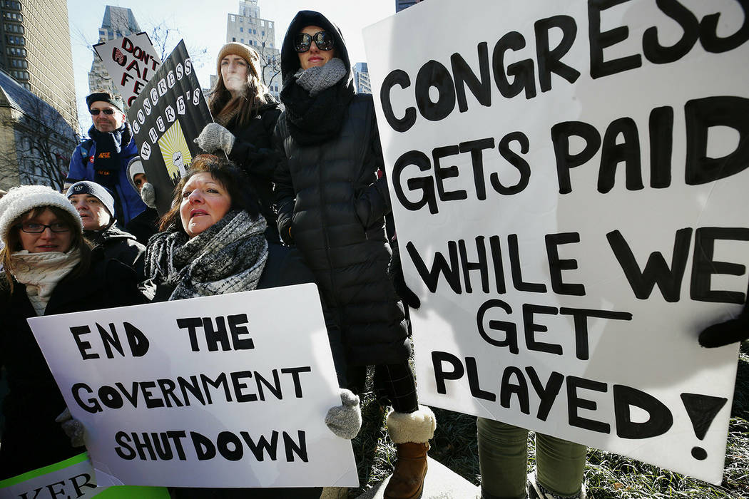 Government workers and their supporters hold signs during a protest in Boston, Friday, Jan.11, 2019. The workers rallied with Democratic U.S. Sen. Ed Markey and other supporters to urge that the R ...