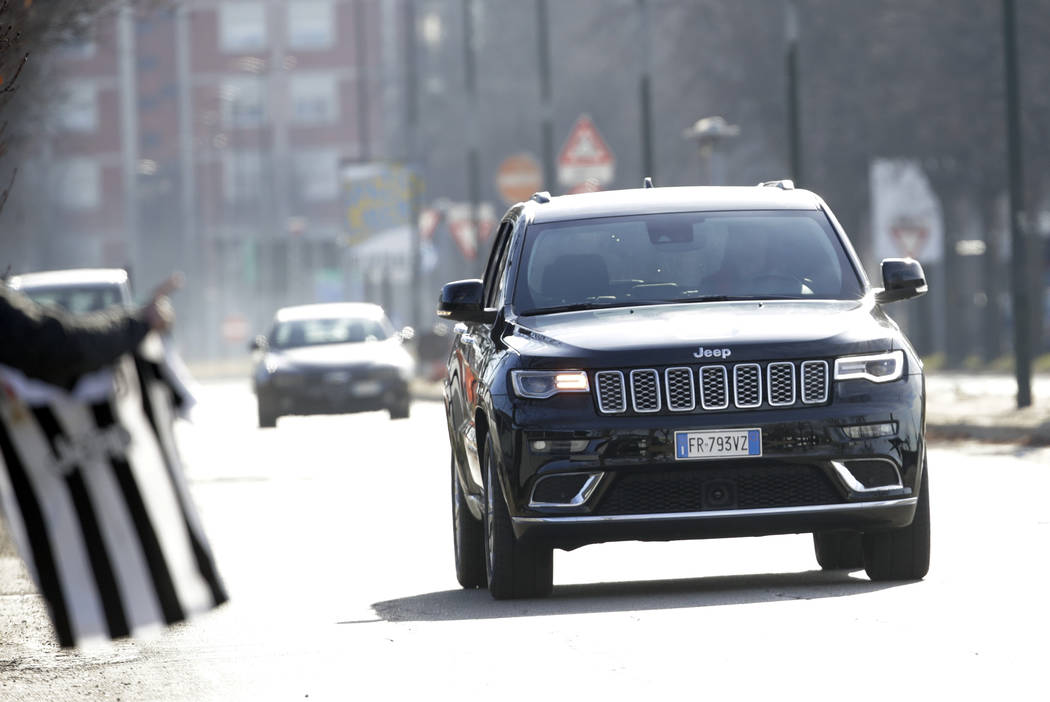 A fan waves a jersey as Juventus' Cristiano Ronaldo drives his car as he arrives for a training session at the Continassa Juventus center, in Turin, Italy, Friday, Jan. 11, 2019. Las Vegas police ...