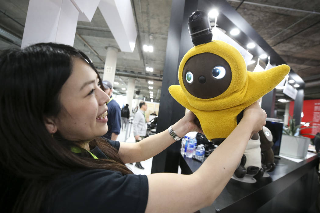 Groove X's Kana Ienaga hugs a Lovot, a home robot that stirs your instinct to love, during a demo at the Groove X booth on the final day CES at the Sands Expo Convention Center in Las Vegas on Fri ...