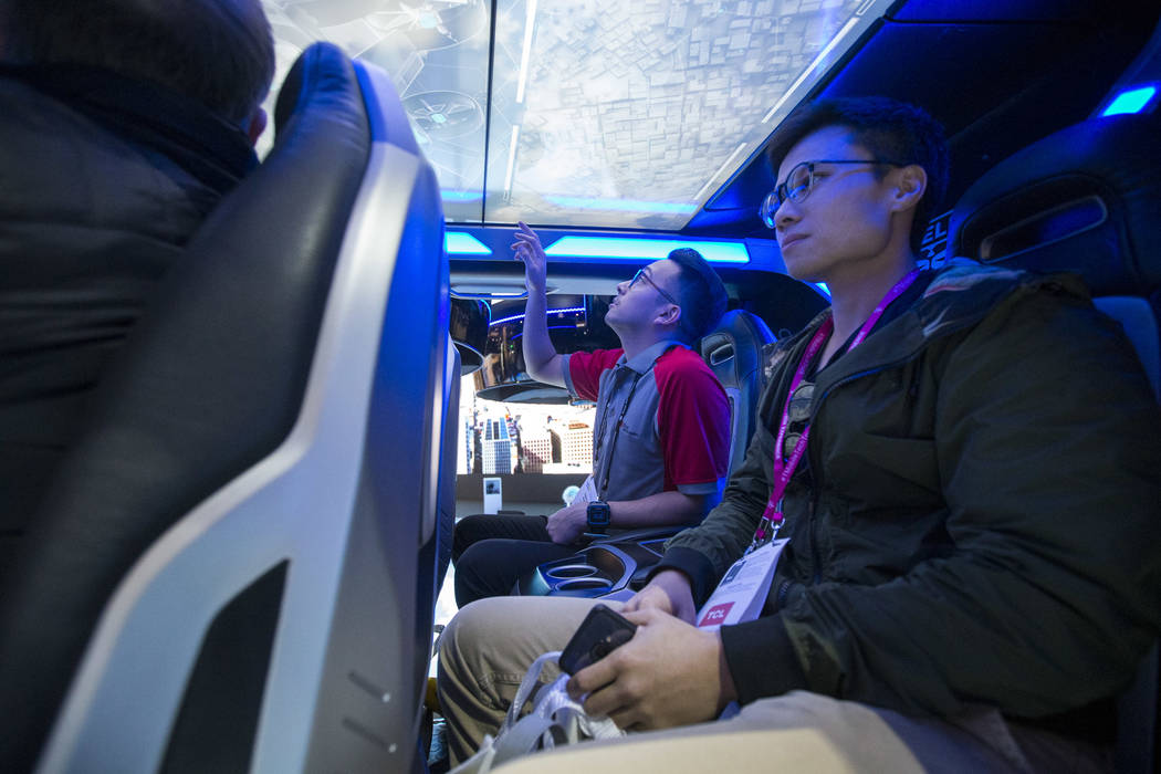 Attendees browse the passenger area of the Bell Nexus, a hybrid-electric air taxi concept, on display on day one of CES at the Las Vegas Convention Center in Las Vegas on Tuesday, Jan. 8, 2019. Ri ...